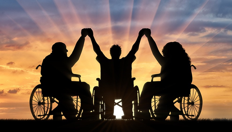 3 people in wheelchairs holding hands