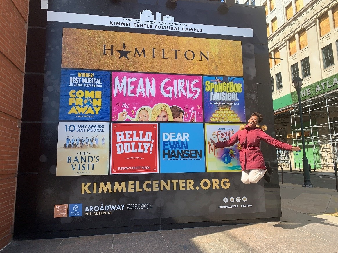 Sydni Jean jumping in front of the 19-20 Broadway Season wall cling.
