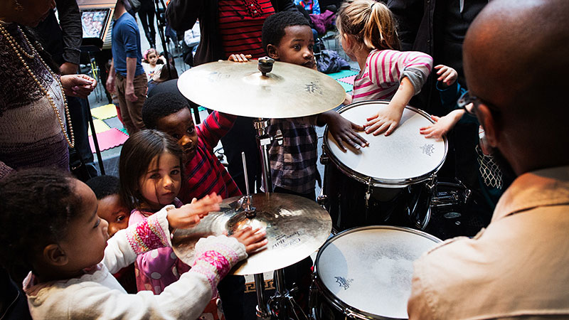 A group of children explore a drum kit at the Kimmel Center