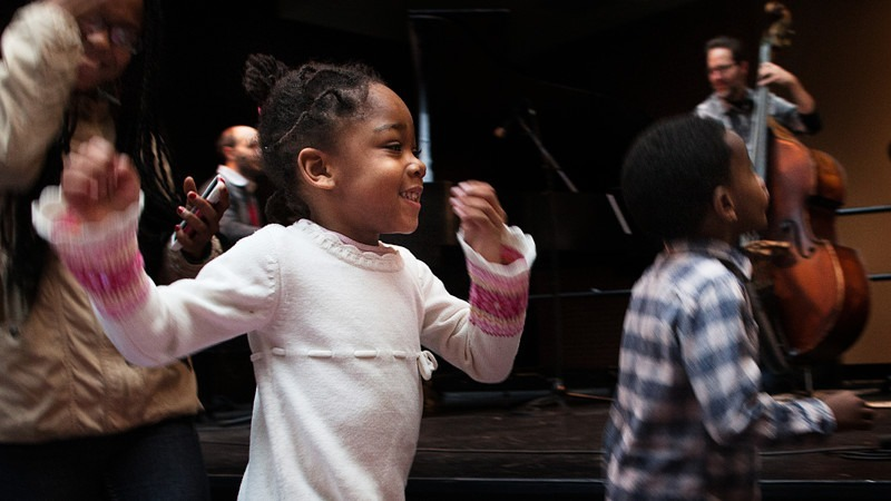 young girl dances with other children while musicians play on stage at the Kimmel Center