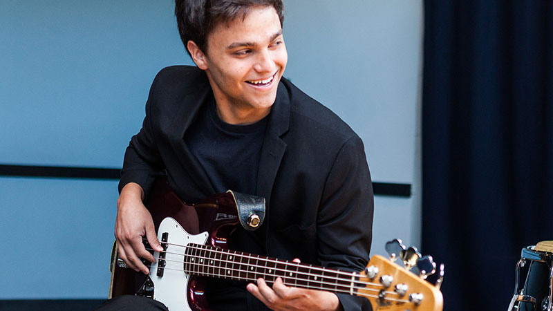 A young man sits and smiles playing the guitar