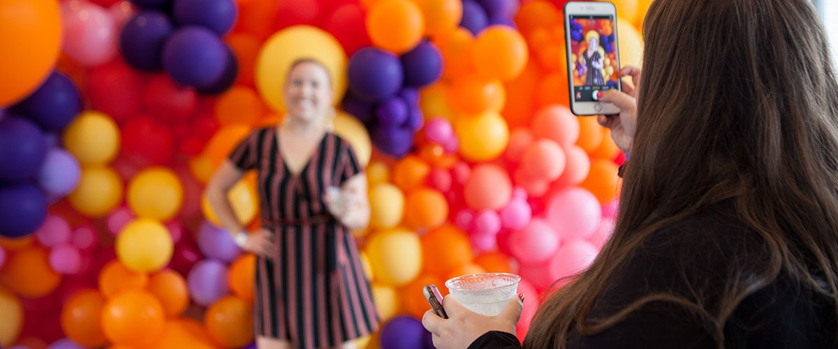 a woman takes a picture of another young woman standing in front of balloons at Balcony Bar