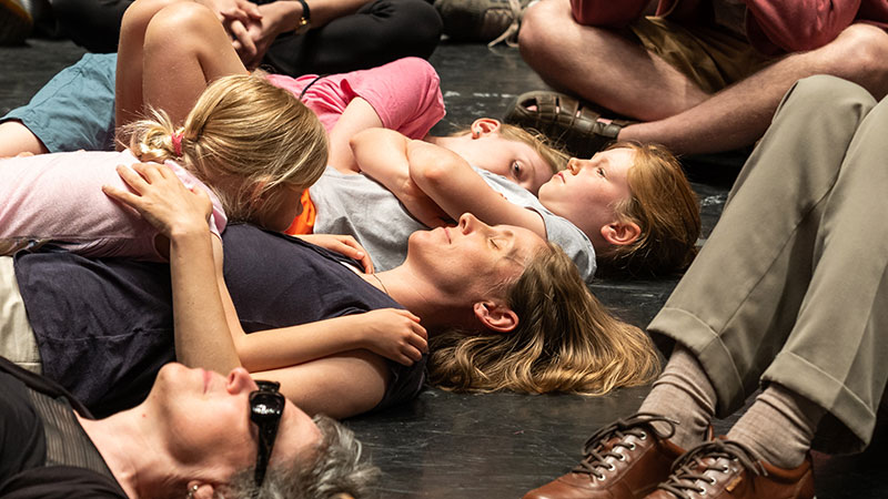 Audience lays on the floor listening to the vibration of the organ