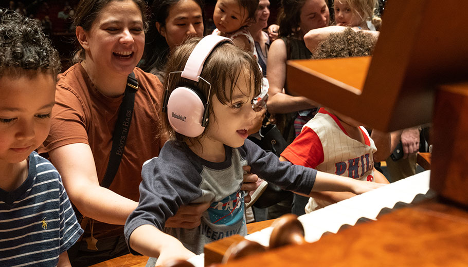 a smiling woman holds a young child trying the organ at the Kimmel Center