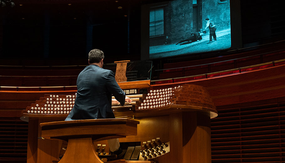 a man plays the organ while a black and white movie movie is playing on a screen