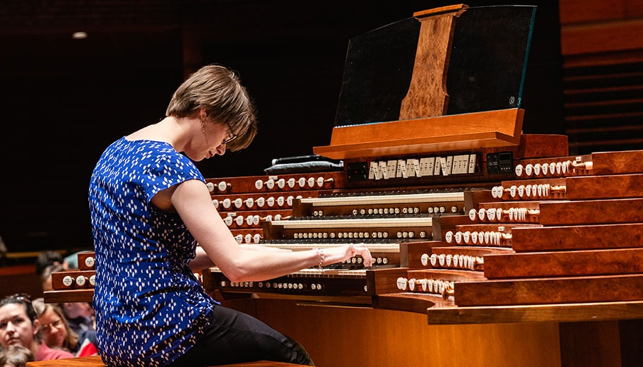 a woman plays the Organ on stage in Verizon hall at the Kimmel Center