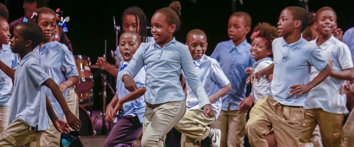A group of school-aged children in school uniforms of light blue shirts and khaki  pants dance on stage