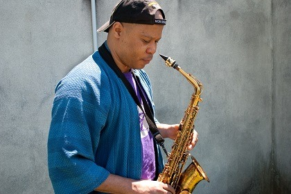 Steve Coleman Stands with alto saxophone looking down
