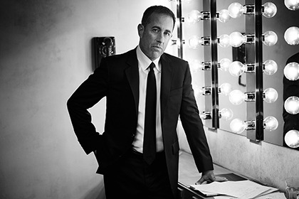 Jerry Seinfeld standing in a dressing room looking at the camera
