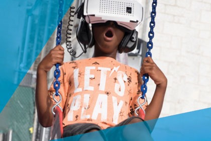 Young boy swings on a swing with VR googles
