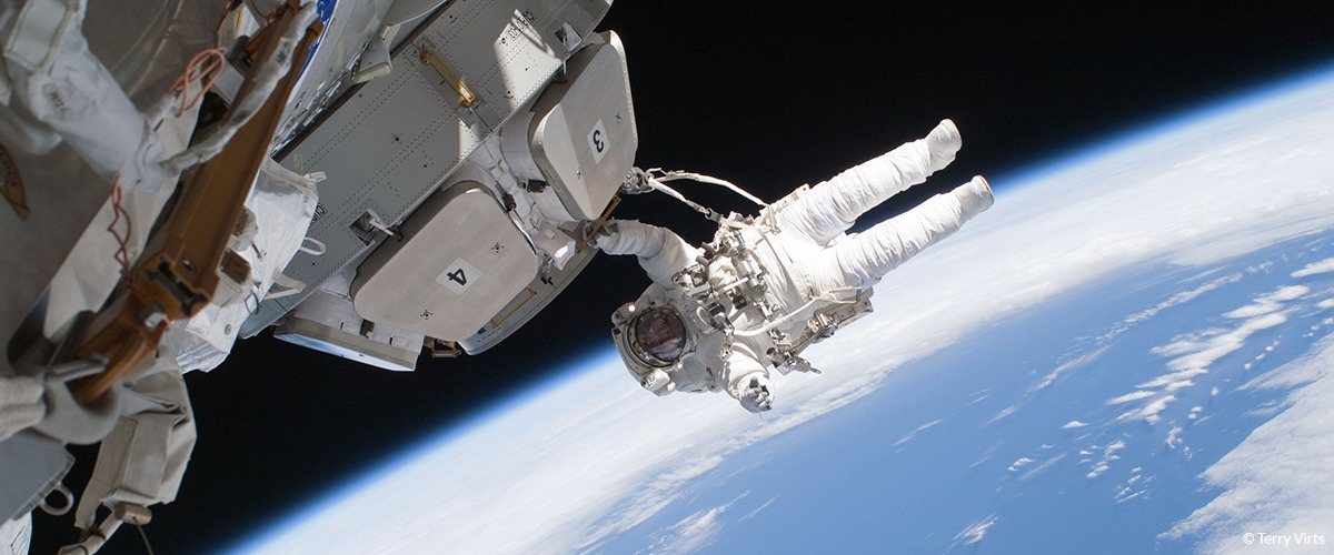 An astronaut floats outside a space vessel in space with earth in the background