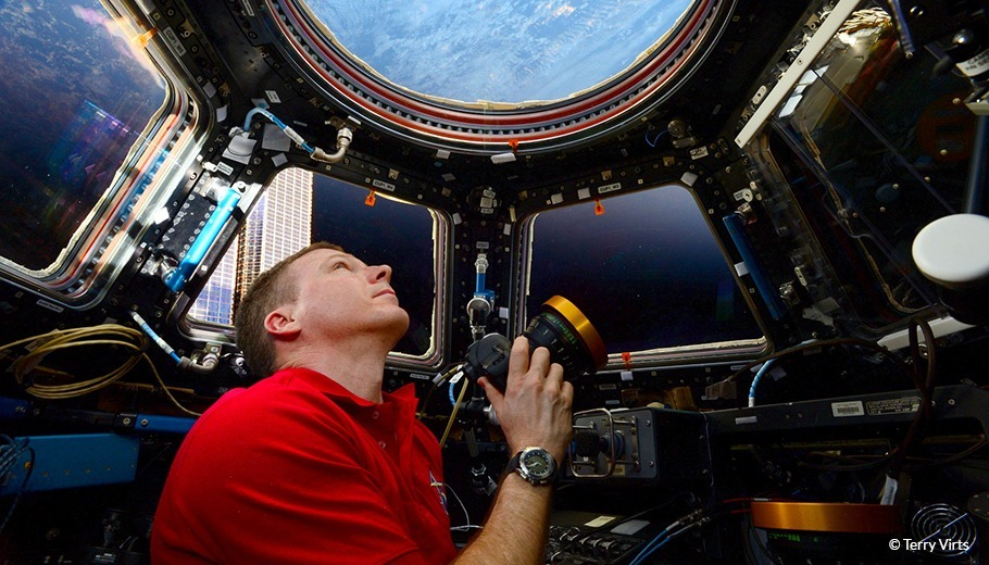 Terry Verts Looks at Earth from a spacecraft holding his camera