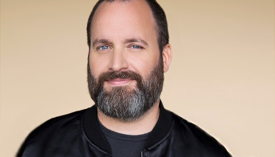 Tom Segura looking at camera in a black jacket with a beige background