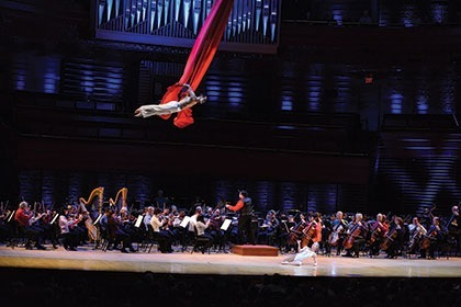 Acrobat performing over orchestra