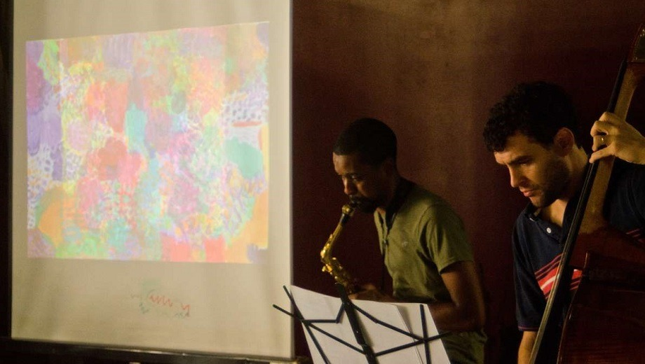two musicians performing sax and bass with artwork projected in the background.