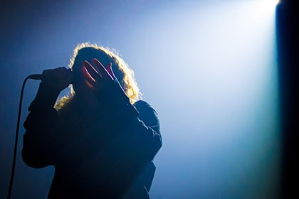 Silhouette of person singing on microphone