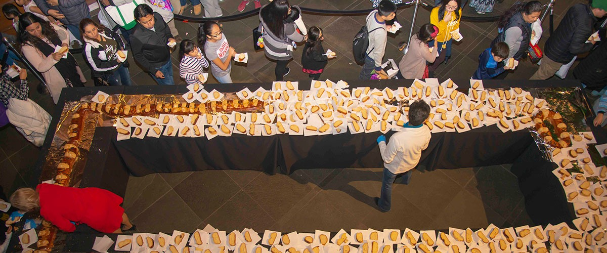"people line up to get a piece of ""Rosca de Reyes"" bread"