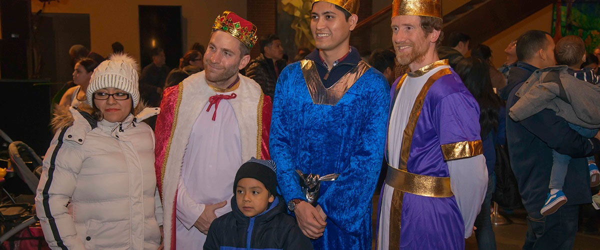 a child poses with the three kings for Three Kings day
