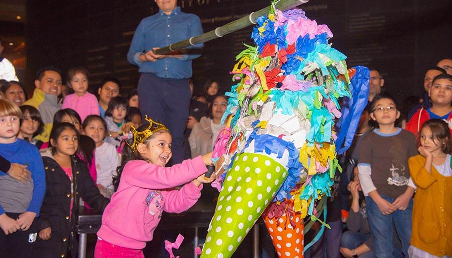 a young girl hits a pinata at the Kimmel Center