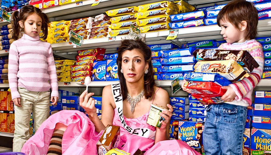 Dena Blizzard pictured in a dress among a mess of groceries with two children standing next to her
