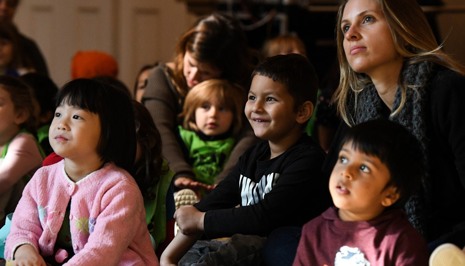 children and parents watching a performance