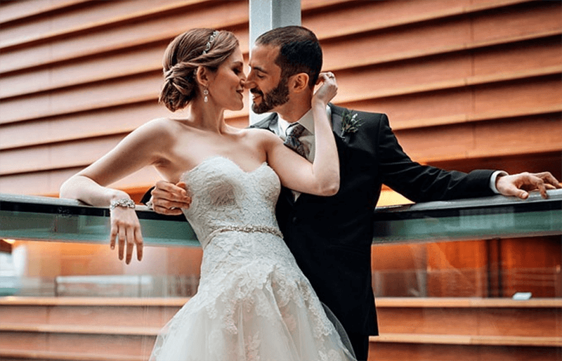 A bride and groom share an intimate moment while standing along one of the Kimmel Center's balconies.