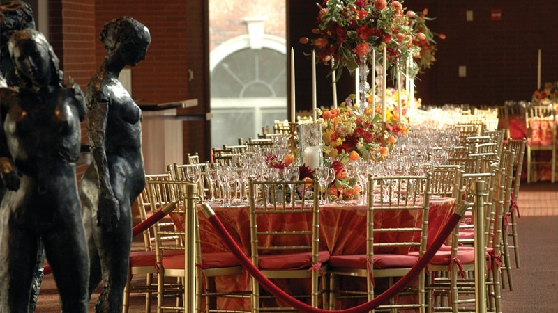Statues and elaborate dining tables set the ambiance for a sophisticated event.
