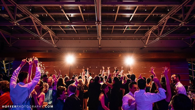 Wedding guests dance and cheer at a reception held in the Hamilton Garden Ballroom.