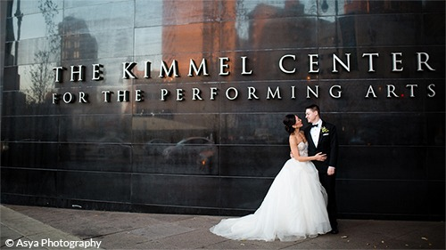 Monica and Andrew in wedding attire stand in front of the Kimmel Center Building Exterior