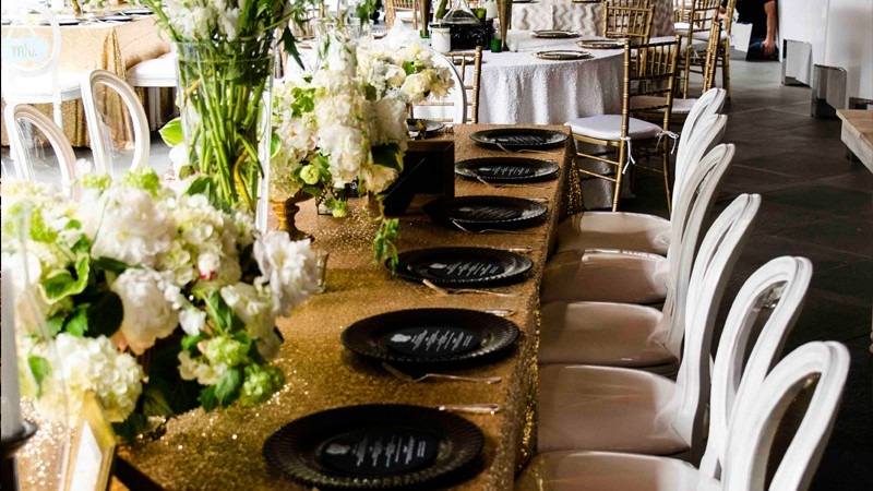 Silverware and flowers decorate the tables of a lovely wedding.