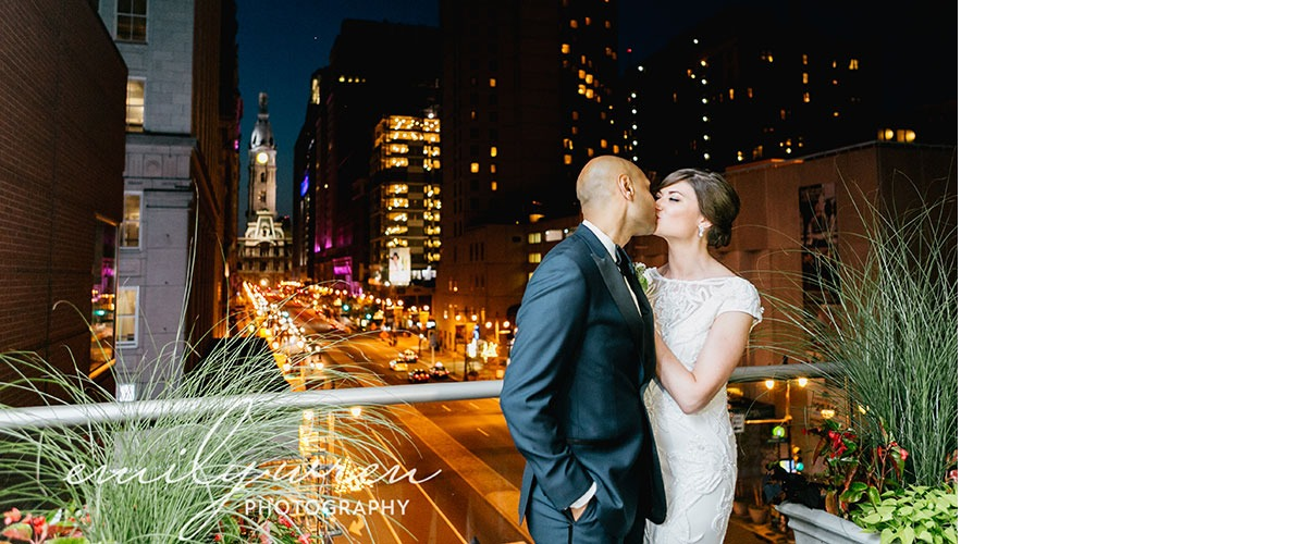 A married couple kiss on the balcony of the Kimmel Center at night overlooking Broad Street and City Hall